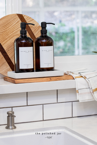 Modern kitchen sink with two The polished Jar amber glass bottle soap dispensers