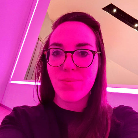 Close up head shot of Rachel Wilson in black turtleneck sweater. Sitting just below a mirror with an LED Strip around the edge which is bathing her in pink light