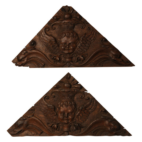 Two oak triangular panels carved with angels, Dutch mid 17th century