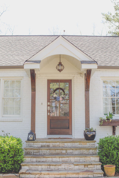 White brick cottage portico front porch exterior with floral front door wreath, stained wood 6 lite glass door, flagstone steps, stained columns, wooden window boxes, nautical copper exterior light.