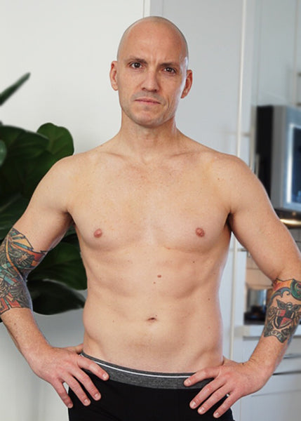 bald man with tattoos in Badami Boxer brief posing for his blog post about toxic masculinity.