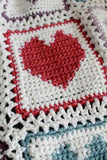 white afghan with colored hearts