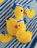 blue afghan with yellow ducks and duck toy and pillow