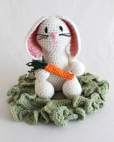 white bunny rabbit with carrot underneath cabbage