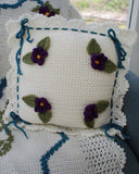 White pillow with purple flowers