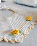 white bib with yellow flowers