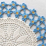 White doily with light blue trim