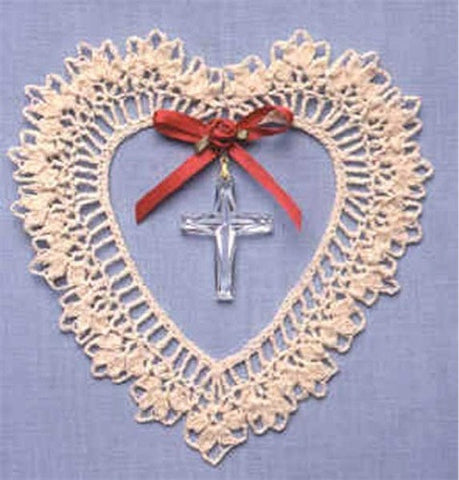 creme sun catcher with red ribbon and cross