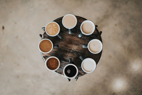 Coffees with varying levels of milk arranged in a circle on a wooden table.