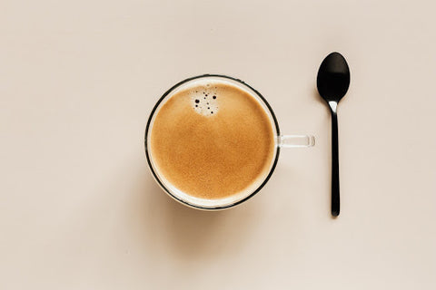 A cup of coffee with a spoon next to it