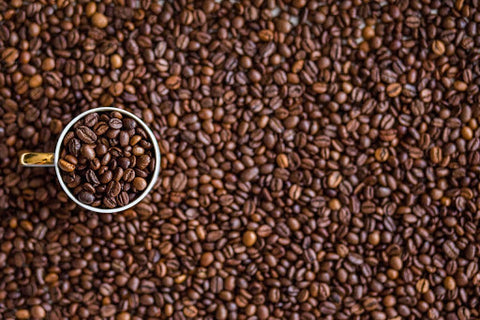 Lots of coffee beans, some in a mug.