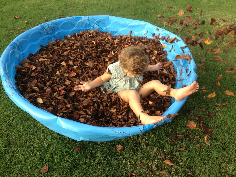 Child playing with leaves in a big sensory bin