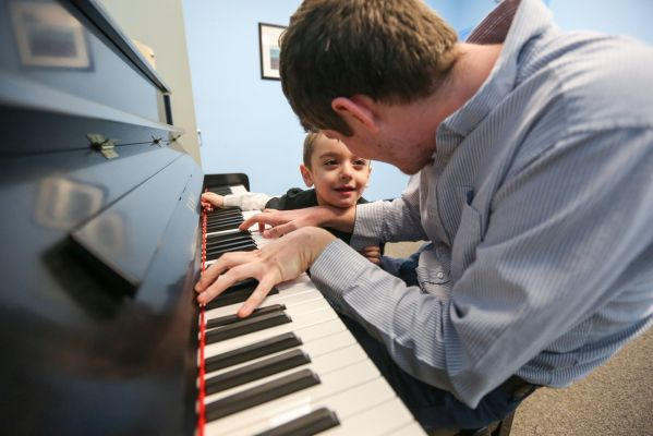 Man plays piano to boy with autism
