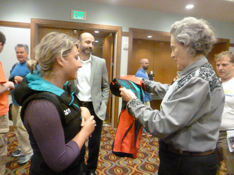 Lisa Fraser giving Temple Grandin her customer Snug Vest to provide Deep Pressure Therapy