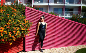 Happy woman standing against pink wall looking at flowers