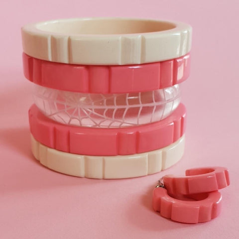hazel bangles in pale pink and ivory stacked with a single thin Corday bangle with hazel earrings to right of shot