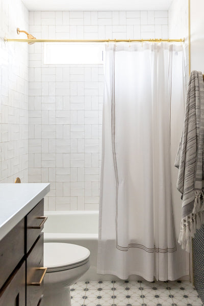 shower with subway tile in crosshatch pattern