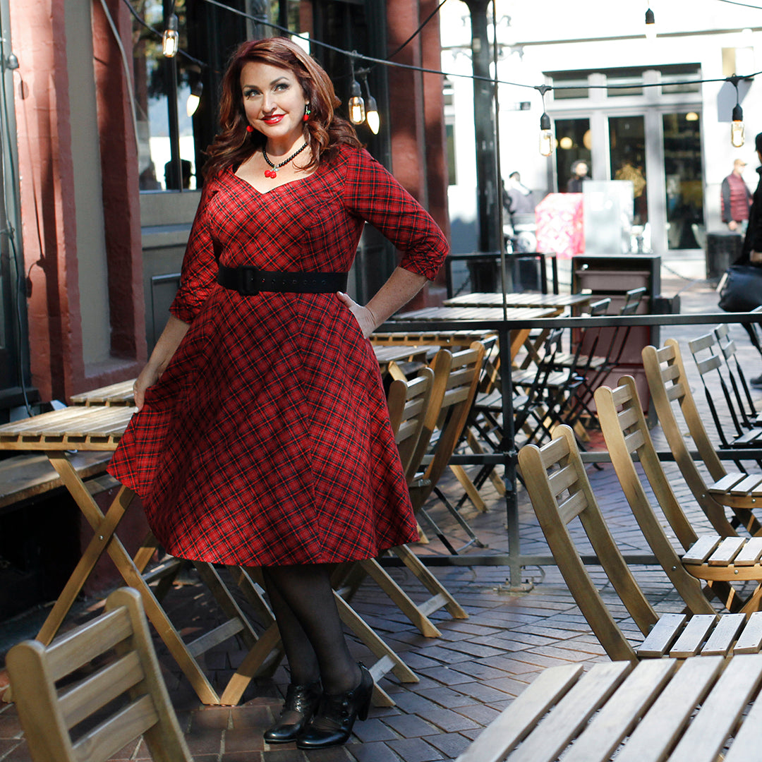 Leah Tuttle models a red plaid Cherry Velvet dress