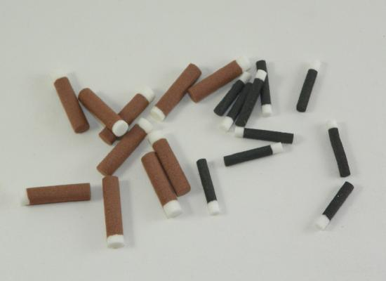 brown or black foam cylinders with white ends used for tying fly fishing flies to imitate ants