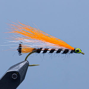 A black orange and white bucktail streamer fishing fly