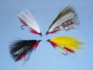 four fishing streamer flies with white, black, olive, and yellow marabou and read throats and tails
