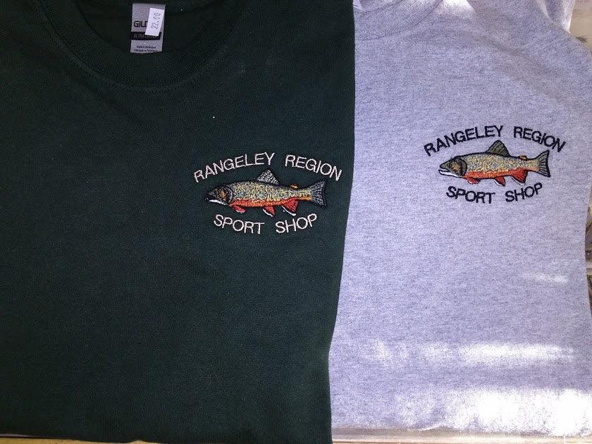 "close up of embroidered design on two long sleeved t-shirt, one gray and one dark green available with embroidered brook trout and shop name ""Rangeley Region Sport Shop"""