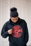 Male model in black pullover hoodie with red thunderbird spindle whorl