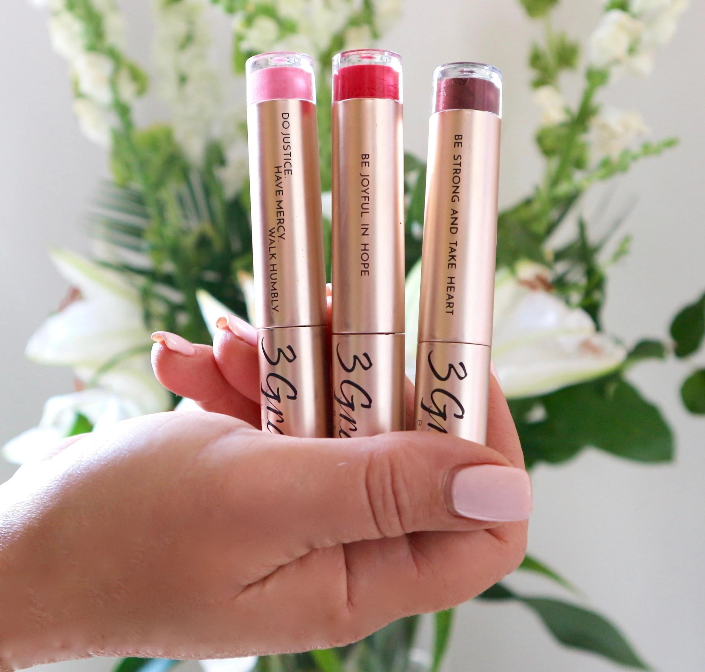 3 Graces Beauty Lipglosses held by a hand