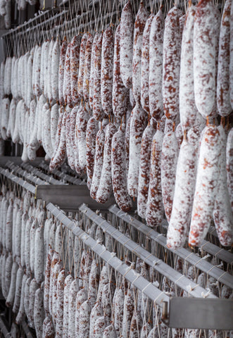 photo of dozens of salami hanging in incubation at Olympia Provisions