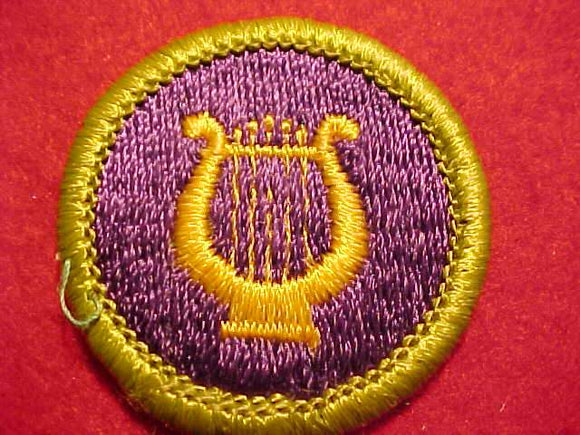 MUSIC, MERIT BADGE WITH CLEAR PLASTIC BACK, GREEN BORDER, NO IMPRINTS/LOGOS IN PLASTIC, 1972-2002