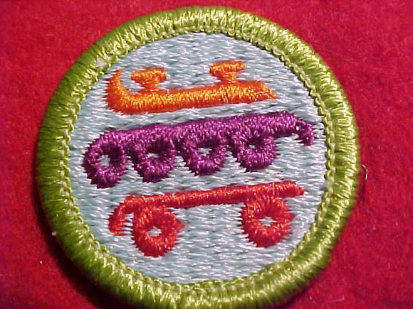 SKATING, MERIT BADGE WITH CLEAR PLASTIC BACK, GREEN BORDER, NO IMPRINTS/LOGOS IN PLASTIC, 1999-2002