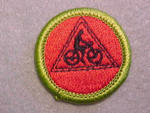 CYCLING- RED BACKGROUND, MERIT BADGE WITH CLEAR PLASTIC BACK, GREEN BORDER, NO IMPRINTS/LOGOS IN PLASTIC