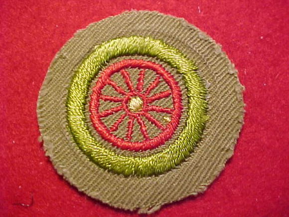 AUTOMOBILING MERIT BADGE (SPOKED WHEEL), CRIMPED EDGE, TAN, ISSUED 1936-43