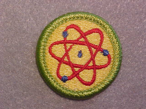 ATOMIC ENERGY, MERIT BADGE WITH CLEAR PLASTIC BACK, GREEN BORDER, NO IMPRINTS/LOGOS IN PLASTIC