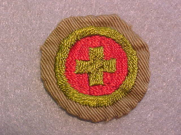 FIRST AID MERIT BADGE, WIDE TAN BORDER, ISSUED 1932-36, USED