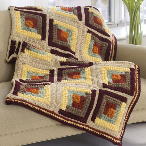 image of crocheted log cabin throw in natural colors of tans and browns draped over the side of a sofa