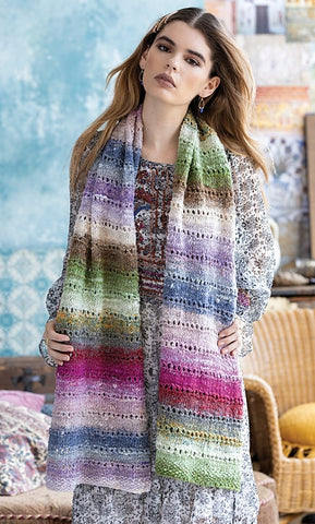 standing woman wearing a long rectangular scarf in soft pastel colors. Striped in festive easter colors of light green, pink, blue and white. the scarf features delicate eyelets every few rows to add a feminine touch