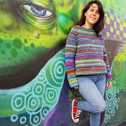 standing woman leaning against a green graffitti wall wearing a hand knit sweater felix pullover designed by amy christoffers in colorful self striping yarn noro ito