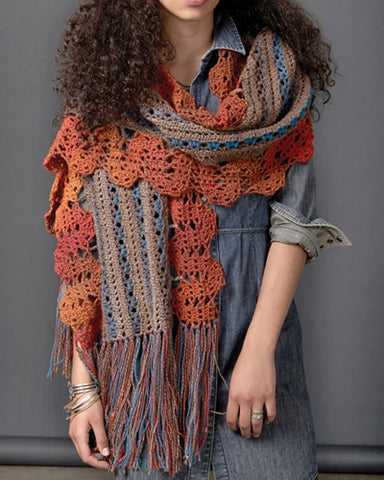 Woman standing wearing a funky bohemian crocheted long rectangular crocheted scarf with a blue and tan center section and along the long edges it features a orange wavy trim. The short ends are finished long tassels to create a fringed edge.