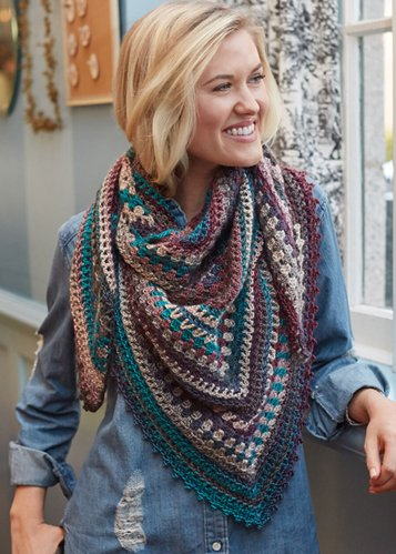 standing blond woman wearing a colorful crocheted cowl in colors of teal purple anf violet