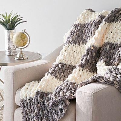 crocheted grey and white striped blanket laying on a chair