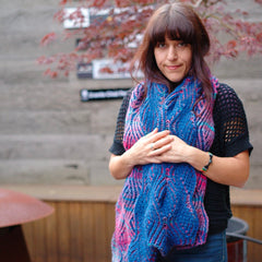 woman wearing nancy marchant's willow brioche scarf knit in shades of blue and purples and pinks