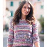 standing brunette woman wearing pullover in bright rainbow colors featuring rows o dropstitches for breezy midrift and arms