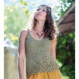 woman standing wearing a hand knitted tank top with tied shoulder straps. The lover hem of the tank top is leaf knitted lace work