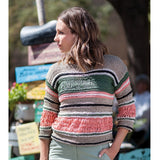 woman wearing ¾ length sleeve pullover in stripes of tan, black, sage green, and salmon pink. the tan is stockinette stitch while the sage green and pink are large drop stitches