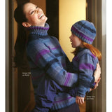 woman laughing and holding a little girl. they are both wearing matching turtleneck hand knit sweaters and beanies