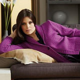 woman laying on her side wearing a bright purple cardigan with large collar