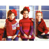 three little girls all lined up with hand knit christmas outfits. one wears a fairs isle red and white sweater with hearts and a matching scarf, the middle one has red stipey knitted dress and the one on the right wears a bright red cardigan with a bumpy textural pattern