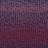 painted sky knitted swatch in pinot noir 223, featuring three colors of yarn plied together shades fo rose pink, blood red, and midnight blue slowly blend together and change colors for a constantly shifting yarn