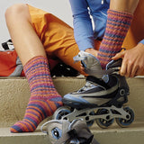image of a kid wearing hand knitted socks in soft orange blue and pink hues putting on rollerblades  from the regia journal 4009 sock pattern pamphlet